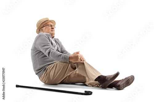 Fototapeta Mature man lying on the floor and holding his knee obraz