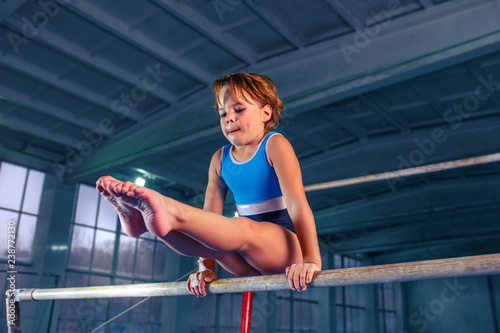 Tela The beautiful little girl is engaged in sports gymnastics on a parallel bars at gym