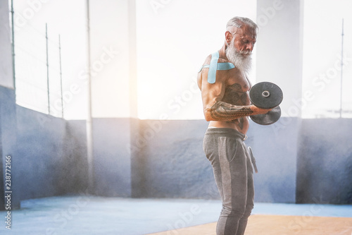 Fotografie, Obraz  Fitness beard man doing biceps curl exercise  inside a gym - Tattoo senior man t