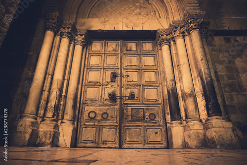 Photo Old wooden door of entrance to the Church of the Holy Sepulchre, also called the Church of the Resurrection or Church of the Anastasis, in Old City of Jerusalem