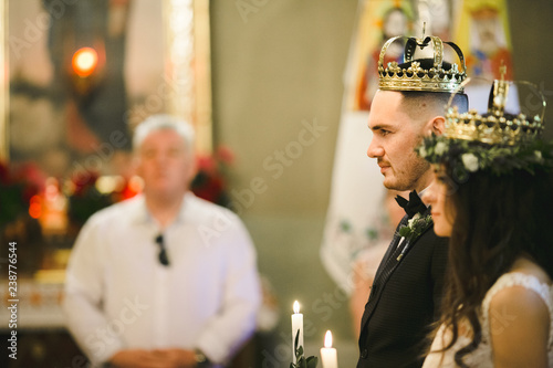 Fotografie, Obraz  Happy bride and groom stand with crowns during ceremony in church