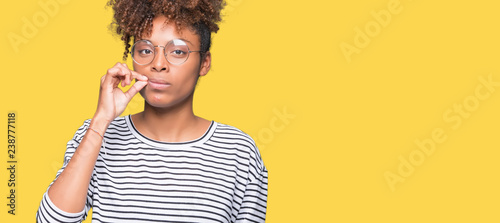 Fotografie, Obraz  Beautiful young african american woman wearing glasses over isolated background mouth and lips shut as zip with fingers
