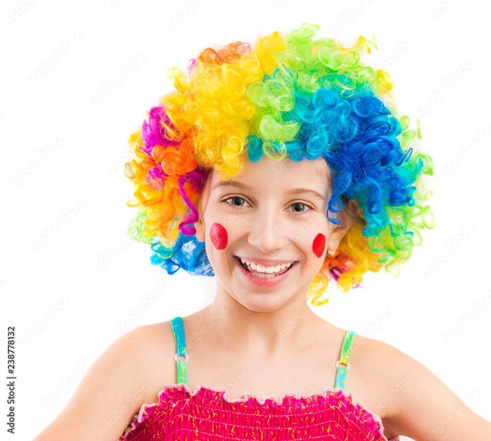 Fototapeta Funny little girl in clown wig with red spots on her cheeks isolated on white background