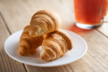 Three Croissants On A White Plate Next To A Cup Of Tea