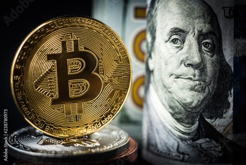 Fototapeta Gold bitcoin coin standing in front of dollar bills. New virtual money concept obraz