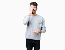 Young Handsome Man Wearing Sweatshirt Over Isolated Background Yawning Tired Covering Half Face, Eye And Mouth With Hand. Face Hurts In Pain.