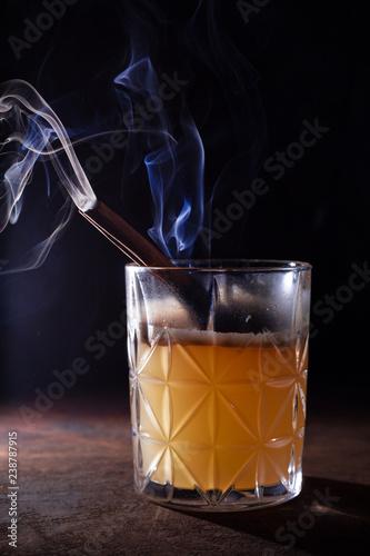 Poster Cocktail Glass of Scotch Whiskey orange juice alcohol cocktail with smoking cinnamon sticks