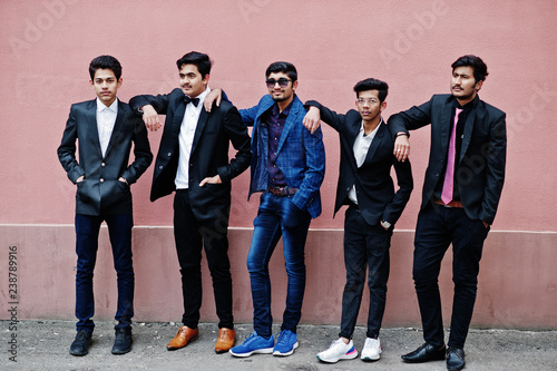 Photo Group of 5 indian students in suits posed outdoor against pink wall