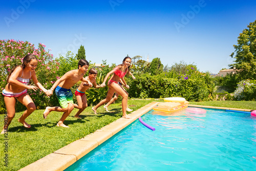 Happy teens running together to swimming pool - Buy this ...