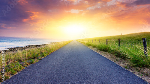 Paved country road . Landscape over clouds sunrise . Sunset above road .