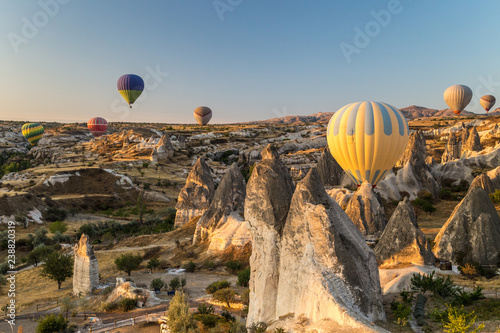 Hot air balloons flying at sunrise over rock formations in Cappadocia, Turkey