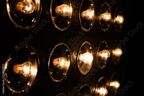 Group of vintage orange bright incandescent bulbs in the studio on a black background Poster Mural XXL