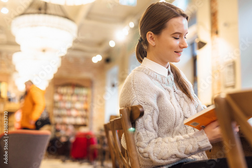 Foto op Plexiglas Bakkerij Clever girl enjoing her time, sit at cafe and read a interesting book. Wear white sweater. Winter, autumn outfit.