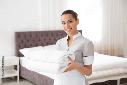 Young chambermaid with clean towels in bedroom Canvas Print