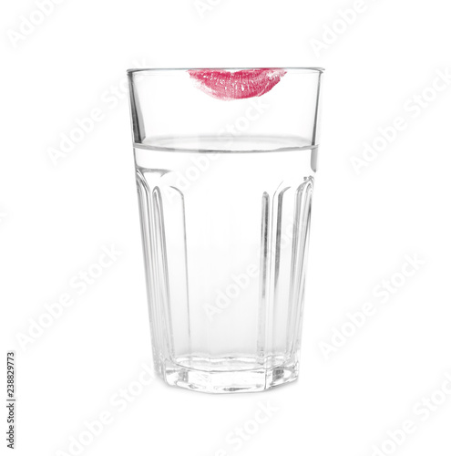 Glass of water with lipstick mark on white background
