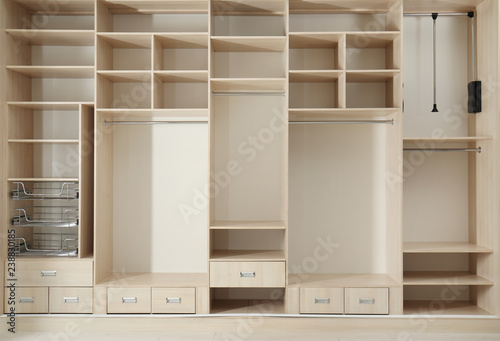 Fotografía  Empty wooden wardrobe with shelves and drawers in dressing room