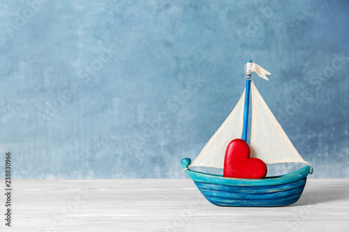 Toy ship with red decorative heart on table. Space for text