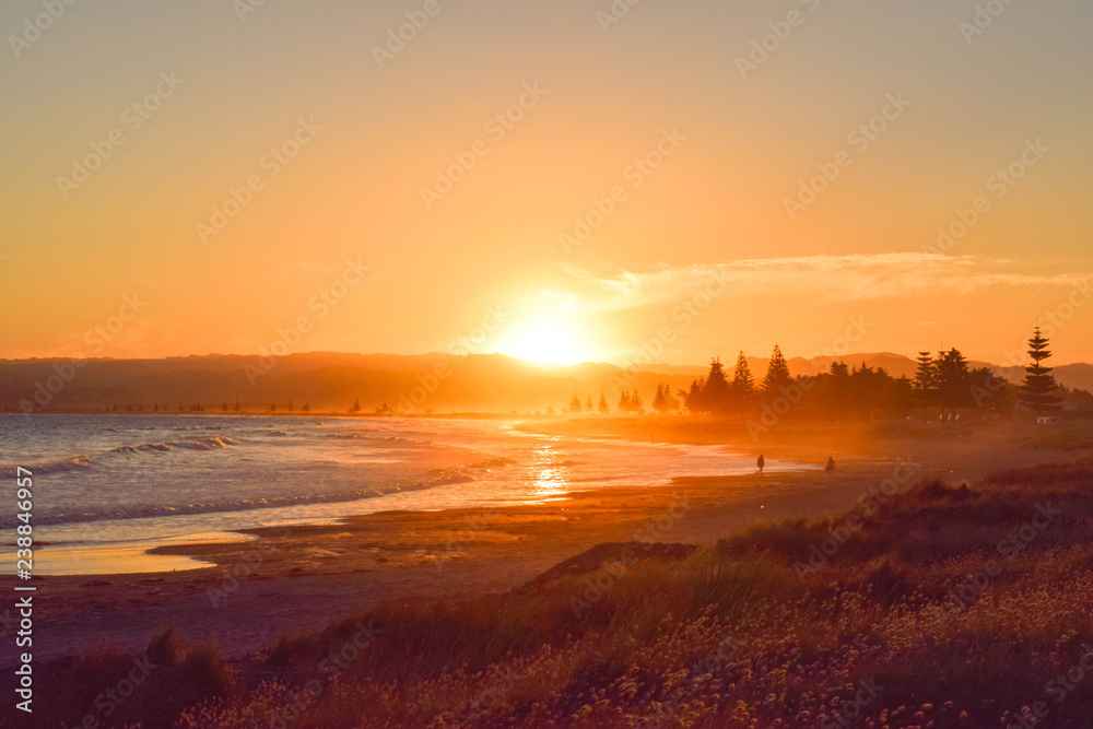 Fototapety, obrazy: Couple walk along the empty beach at sunset in Gisborne, New Zealand.