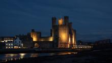 Caernarfon Castle, Often Anglicized As Carnarvon Castle, Is A Medieval Fortress In Caernarfon, Gwynedd, North-west Wales. Taken Here Lit Up At Night
