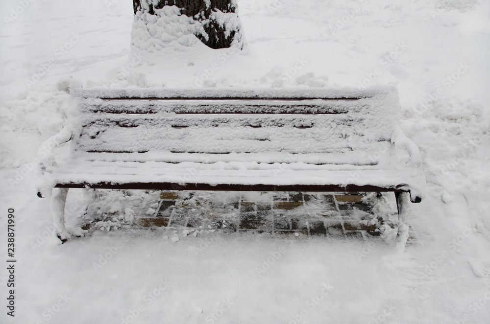 the bench in the park is covered with white snow