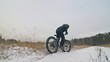 Professional extreme sportsman biker riding fat bike in outdoors. Close-up view of rear wheel. Cyclist ride in winter forest. Man on mountain bicycle with big tire. Snow fly into the lens camera.