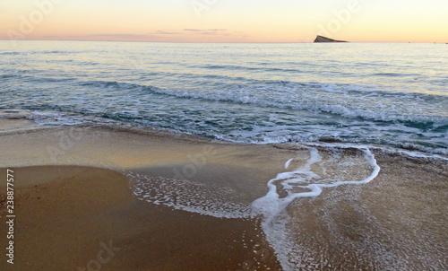Isla y playa de Benidorm al atardecer con ola espumosa sobre la orilla. Alicante.