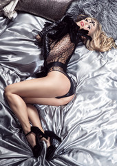 young lady in glamour outfit is laying in a bed