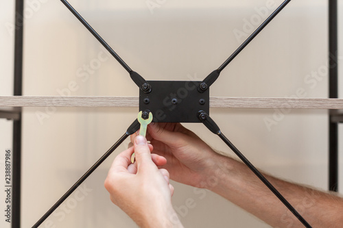 Fotografie, Tablou  The handyman adds the bookcase construction by screwing the bolts with a hexagon