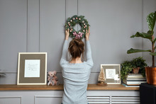 Girl Hanging A Wreath On A Gray Wall, Sun Light