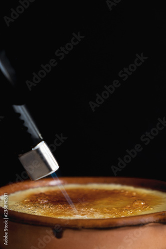 Fotografiet  Burning sugar on a caramel custard surface with a home blowtorch in a clay pot with black background