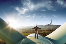 Happy Engineer Feel Success After Good Work. He Standing A Top Of Windmill And Looking Beautiful Sunset