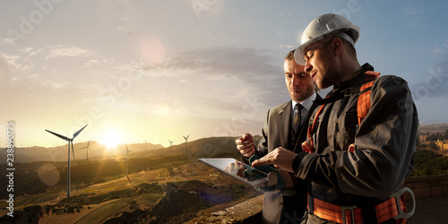 Windmill engineer and businessman planing new ecology project. they standing and looking in tablet. Around wind generators