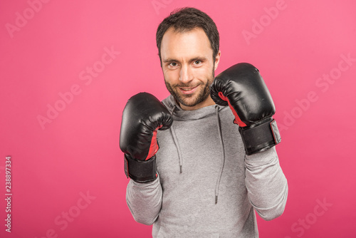 handsome smiling boxer posing in box gloves, isolated on pink Wallpaper Mural