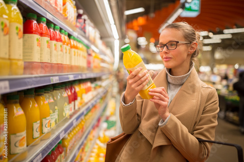 Pretty, young woman shopping for her favorite fruit juice/smoothie at a grocery store