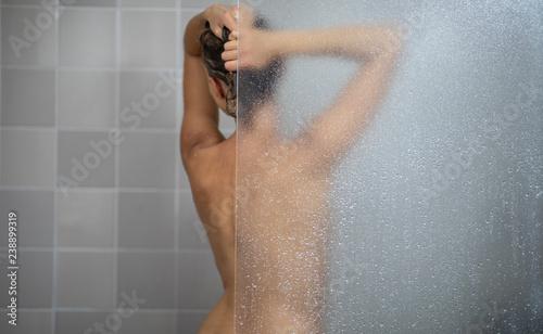 Obraz na plátně Woman taking a long hot shower washing her hair in a modern design bathroom