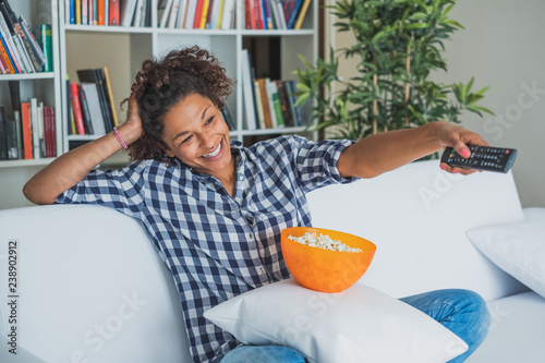 Fotografie, Tablou  Black woman watching tv at home and holding a remote control