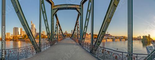 Fototapeta kładka  eiserner-steg-slynna-zelazna-kladka-dla-pieszych-przecina-rzeke-men-we-frankfurcie-z-panorama-rano