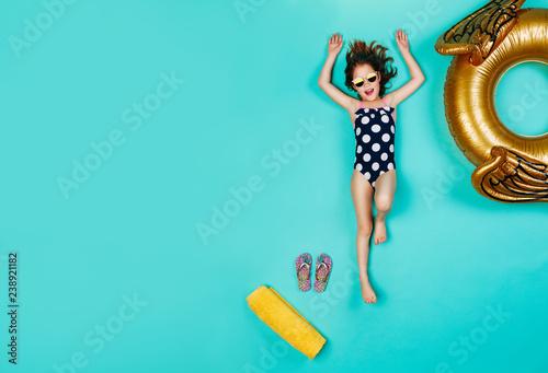 Fotografia, Obraz Happy girl in swimsuit lying on blue background