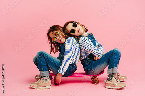 Fotografie, Obraz  Adorable girls sitting together on a skateboard