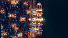 Crane Shipping Container At Night, Aerial Top View Container Ship Carrying Container Import And Export Business Logistic And Transportation.