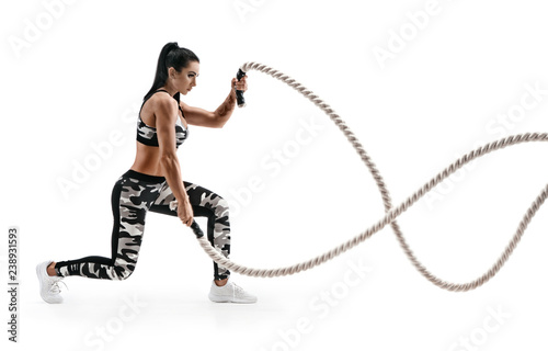 Strong woman workout with battle ropes. Photo of latin woman in military sportswear isolated on white background. Strength and motivation. Side view.