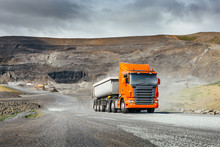 Modern Orange European Truck With White Heavy Duty Dump Trailer Drives After Load From Quarry In A Sunny Day