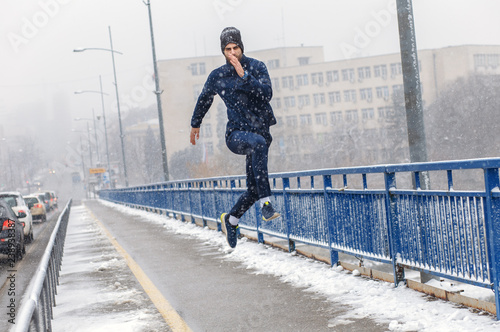 Young man running in city street at cold winter day.