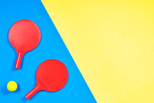 Red Tennis Rackets With Ball On Blue And Yellow Background