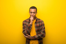 Young African American Man On Vibrant Yellow Background Looking Down With The Hand On The Chin