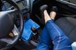 women's feet in high heels inside the car