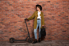 Young Beautiful Woman In Trench Coat,jeans And Black Hat Holding Backpack In Hand While Happily Looking On Electric Scooter Over Brick Wall Background