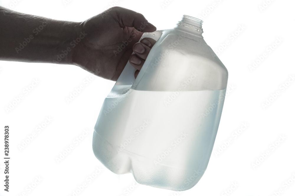 Fototapety, obrazy: Hand holding 1 gallon plastic bottle of drinking water; silhouette on white.