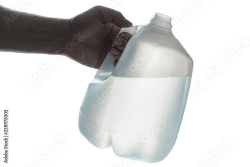 Fototapeta Hand holding 1 gallon plastic bottle of drinking water; silhouette on white. obraz