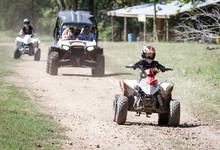 Child On Quad ATV With Parents In UTV On Dirt Road